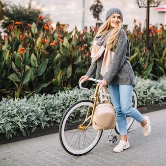 Femme joyeuse, marche à vélo près de parterre de fleurs