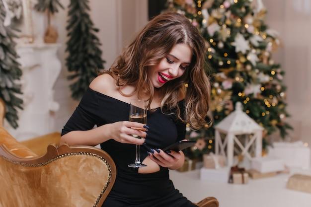 Femme joyeuse avec message texto de longs cheveux brillants dans la nuit du nouvel an. portrait intérieur d'une fille à la mode en robe noire boit du champagne et tenant le téléphone près de l'arbre de noël.