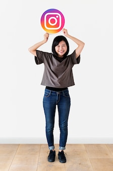 Femme joyeuse montrant une icône instagram