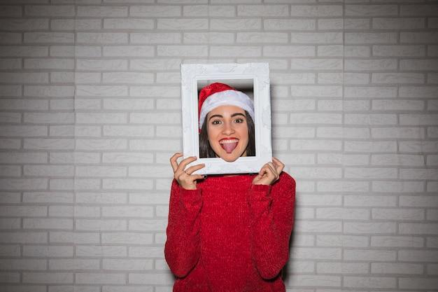 Femme joyeuse montrant la langue dehors dans le cadre