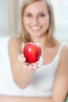 Femme joyeuse montrant une pomme