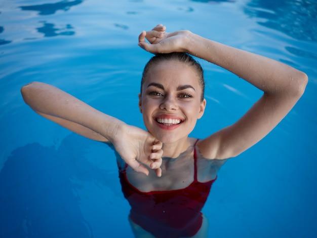 Une femme joyeuse nage dans la piscine et un sourire de maillot de bain rouge