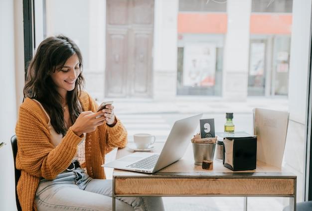 Femme joyeuse, naviguant sur smartphone au café