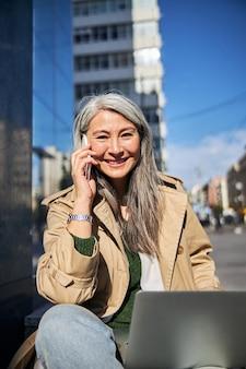 Femme joyeuse avec ordinateur portable parlant au téléphone portable à l'extérieur