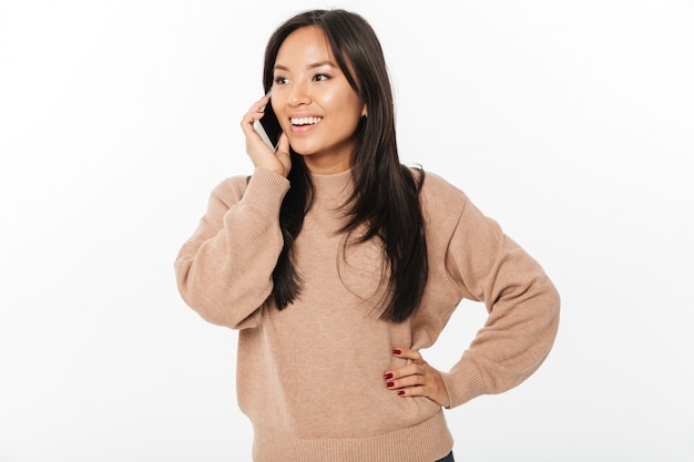 Femme joyeuse, parlant par téléphone mobile. en regardant de côté.