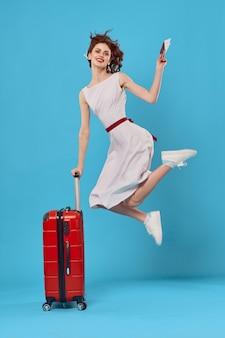 Femme joyeuse passager bagages aéroport vol fond bleu. photo de haute qualité