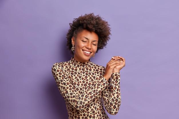 Femme joyeuse à la peau foncée optimiste avec une coiffure frisée, sourit largement et ferme les yeux, garde les mains jointes, porte une tenue léopard