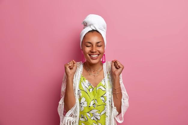 Femme joyeuse avec une peau foncée saine et un sourire à pleines dents lève les poings fermés