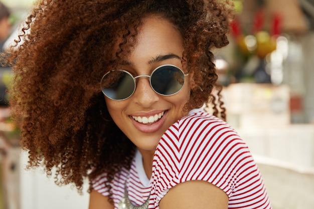 Une femme joyeuse à la peau sombre et aux cheveux bouclés, porte des lunettes de soleil et un t-shirt rayé, étant de bonne humeur lorsqu'elle rencontre des amis à la cafétéria, profite des vacances de villégiature et d'été. repos, concept d'émotions
