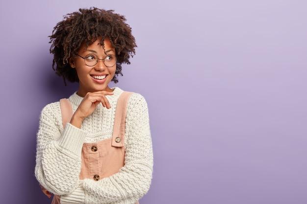 Une femme joyeuse à la peau sombre a une expression réfléchie, garde la main sous le menton, a un regard tendre doux, sourit poliment, attend le client dans la boutique, vêtue d'une tenue à la mode, isolée sur un mur violet