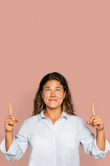 Femme joyeuse pointant vers le haut et souriant