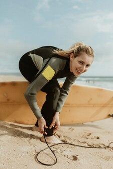 Femme joyeuse portant une laisse de planche de surf