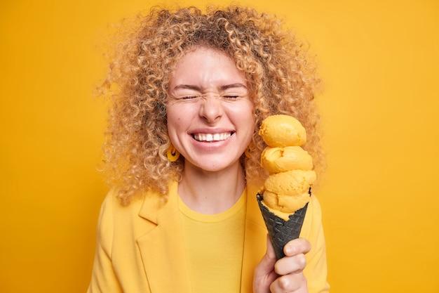 Une femme joyeuse et positive aux cheveux bouclés ferme les yeux des sourires de bonheur et tient largement une délicieuse crème glacée appétissante au goût de citron dans une gaufre exprime des émotions authentiques sincères. tir monochrome.