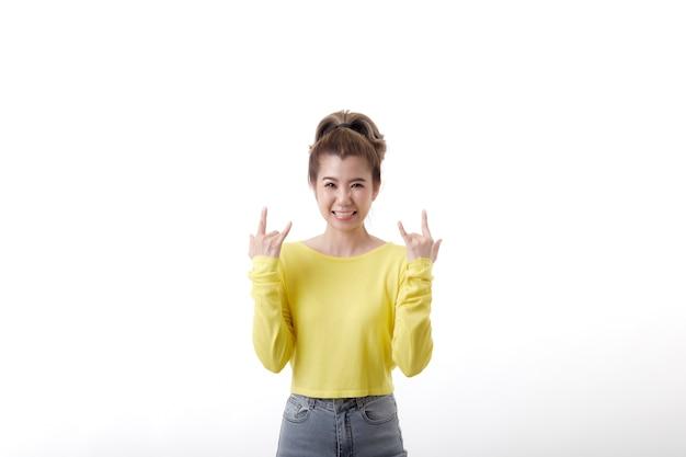 Femme joyeuse positive aux cheveux courts fait signe de métal lourd portant un pull moutarde