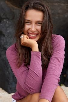 Femme joyeuse positive avec une expression faciale heureuse, vêtue d'un pull décontracté, sourit positivement