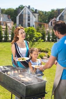 Femme joyeuse positive regardant son mari tout en tenant une assiette