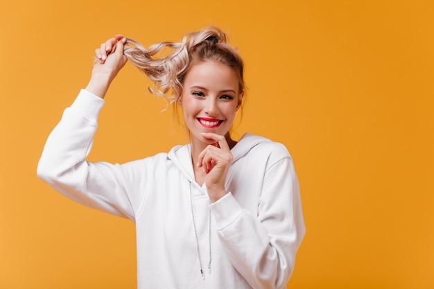 Une femme joyeuse en prévision de bonnes nouvelles se mord la lèvre