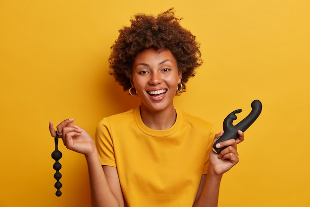 Une femme joyeuse profite d'un massage intime, pose avec un gode et des boules anales, utilise un vibrateur vaginal clitoridien pour se satisfaire, utilise des jouets sexuels pour la masturbation, maintient la santé des femmes