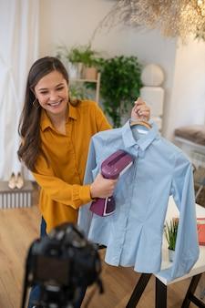 Femme joyeuse ravie à l'aide du bateau à vapeur tout en faisant les tâches ménagères à la caméra