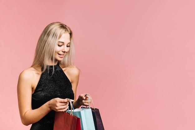 Femme joyeuse à la recherche dans un sac en papier