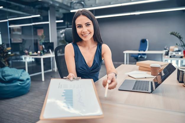 Une femme joyeuse remet un document et un stylo pour signature