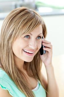 Femme joyeuse répondant au téléphone dans la cuisine
