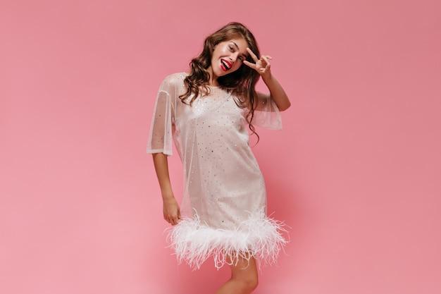 Une femme joyeuse en robe blanche sourit largement sur un mur rose