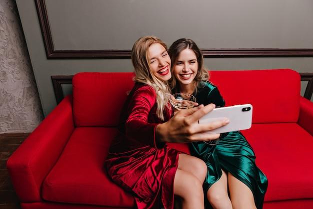 Femme joyeuse en robe rouge assise sur le canapé et faisant sefie. rire des filles en tenue élégante posant sur un canapé.