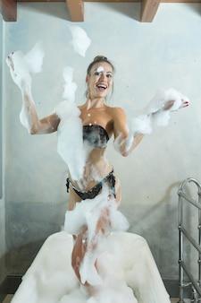Femme joyeuse s'amusant avec de la mousse dans la baignoire