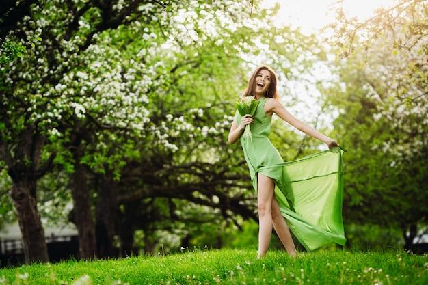 Femme joyeuse saute dans un jardin verdoyant