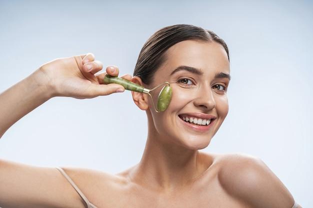 Femme joyeuse se donnant un massage du visage