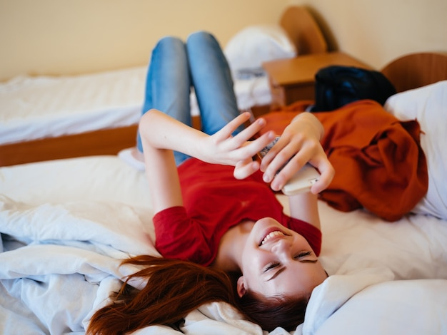 Une femme joyeuse se trouve à la maison sur le lit avec la communication téléphonique
