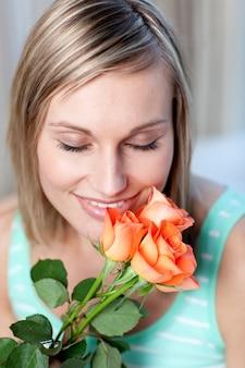 Femme joyeuse, sentant les roses