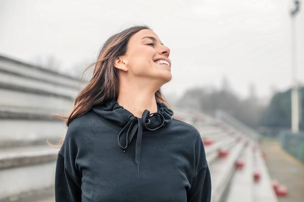 Femme joyeuse, souriant au terrain de sport