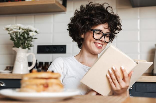 Femme joyeuse souriante ayant un délicieux petit-déjeuner assis à la cuisine à la maison, lisant un livre