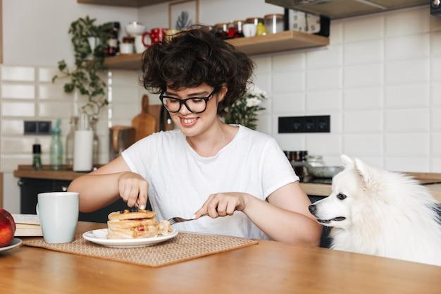 Femme joyeuse souriante ayant un délicieux petit déjeuner assis à la cuisine à la maison, manger des crêpes