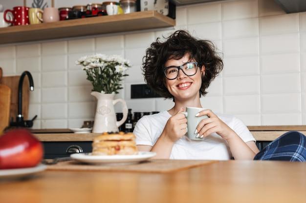 Femme joyeuse souriante ayant un petit déjeuner savoureux assis à la cuisine à la maison, boire du café