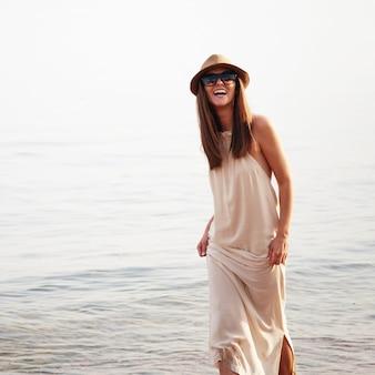 Une femme joyeuse souriante mignonne passe des vacances d'été sur une plage de la mer