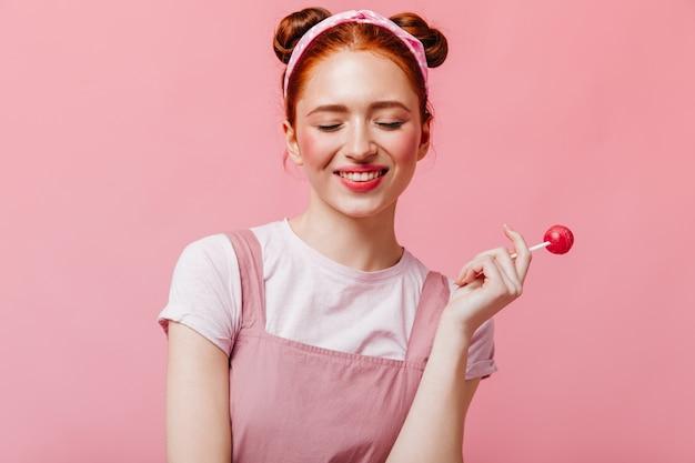 Femme joyeuse en t-shirt blanc et haut sourit et détient des bonbons sur fond rose.