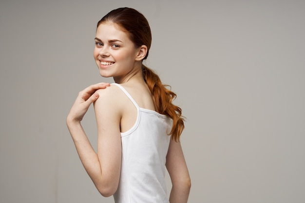 Une femme joyeuse en t-shirt blanc se réchauffe