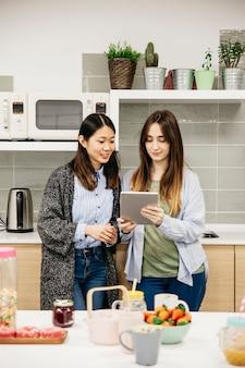 Femme joyeuse avec tablette dans la cuisine