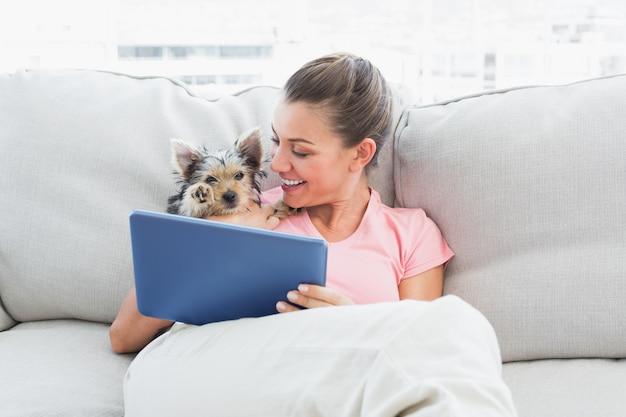 Femme joyeuse avec tablette avec son yorkshire terrier