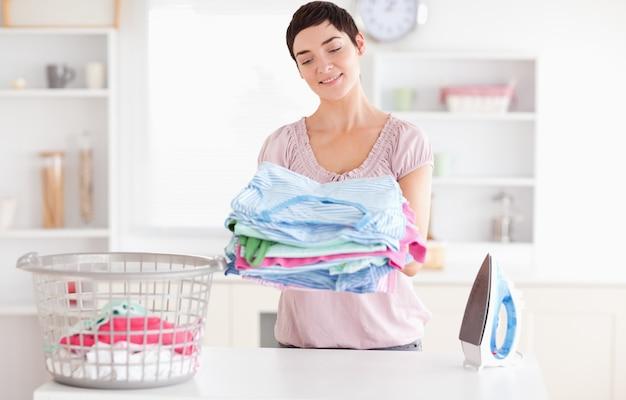 Femme joyeuse avec un tas de vêtements
