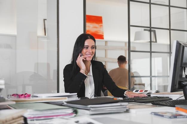 Femme joyeuse avec téléphone à la table de bureau