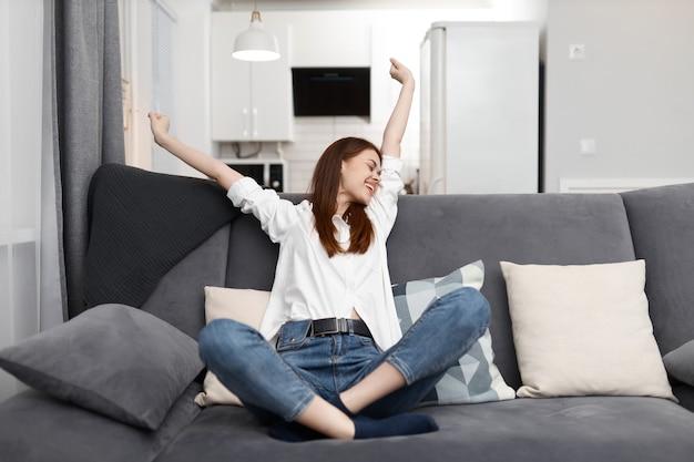 Femme joyeuse tenant ses mains au-dessus de sa tête à la maison sur le canapé week-end de vacances