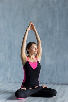 Femme joyeuse tendre ses mains en position assise