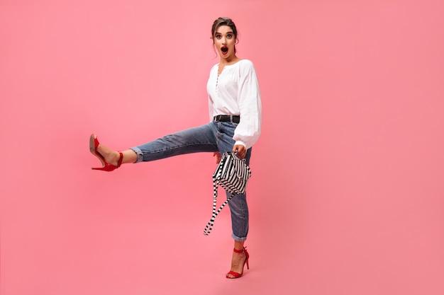 Femme joyeuse en tenue élégante se déplace sur fond rose. fille de mode jeune avec chemise blanche lèvres rouges et jeans légers posant sur fond isolé.