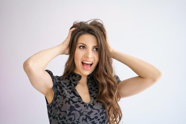 Une femme joyeuse tient sa tête avec ses mains en surprise sur fond blanc