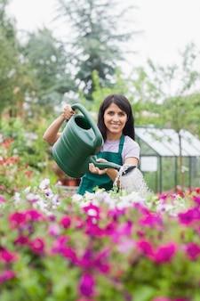 Femme joyeuse travaillant dans le centre du jardin arrosant les plantes