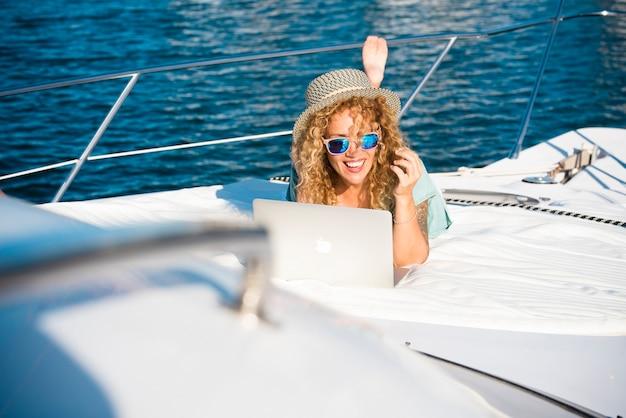 Une femme joyeuse travaille en plein air avec un ordinateur portable allongée sur un bateau bénéficiant de la liberté et d'une connexion internet - concept de personnes et de mode de vie moderne et intelligent - nouveau concept de bureau d'emploi